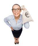 Empresaria feliz que sostiene el bolso del dinero con euro Imagen de archivo libre de regalías