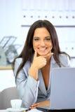 Empresaria feliz que trabaja con la computadora portátil imagen de archivo libre de regalías