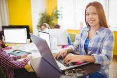 Empresaria feliz que trabaja con la computadora portátil Fotografía de archivo