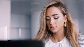 Empresaria feliz que trabaja en su ordenador portátil en la oficina almacen de video