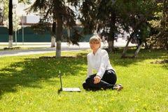Empresaria feliz que usa el ordenador portátil en un parque de la ciudad Fotografía de archivo