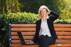 Empresaria feliz que usa la computadora portátil Imagen de archivo