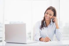 Empresaria feliz que usa la computadora portátil en su escritorio Imagenes de archivo