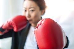 Empresaria fuerte y independiente en un traje de negocios y los guantes de boxeo que miran amenazador la cámara fotos de archivo