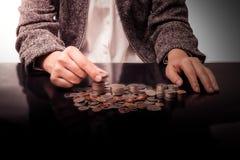 Empresaria Hand Put Coins a la pila de monedas Imagenes de archivo
