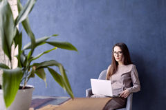 Empresaria hermosa con el pelo largo usando el ordenador portátil moderno mientras que se sienta en su oficina moderna del desván fotografía de archivo libre de regalías