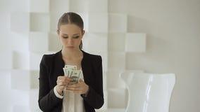 Empresaria hermosa en traje formal que cuenta de nuevo la pila de dólares almacen de metraje de vídeo