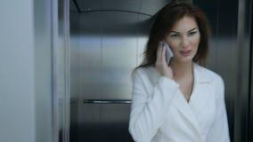 Empresaria hermosa en traje que camina del elevador y del teléfono celular que habla metrajes