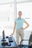 Empresaria hermosa feliz que presenta en su oficina con la mano en cadera Fotos de archivo libres de regalías