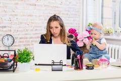 Empresaria hermosa joven alegre que mira el ordenador portátil mientras que se sienta en su lugar de trabajo con su pequeña hija Fotos de archivo libres de regalías