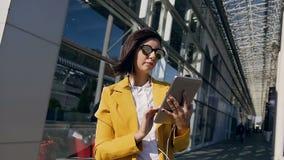 Empresaria hermosa joven en auriculares usando la situación de la tableta en la calle urbana en el centro de negocio almacen de metraje de vídeo