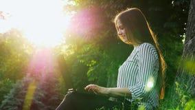 Empresaria hermosa joven que mecanografía en un ordenador portátil, sentándose en la hierba cerca de árbol, cuaderno del uso de l almacen de metraje de vídeo