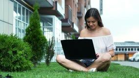 Empresaria hermosa joven que mecanografía en un ordenador portátil, sentándose en la hierba cerca de hotel, cuaderno del uso de l almacen de metraje de vídeo