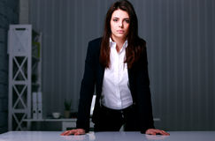 Empresaria hermosa joven que se coloca cerca de la tabla Fotos de archivo