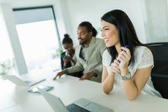 Empresaria hermosa joven que se sienta en un escritorio de oficina con la cuesta Fotografía de archivo libre de regalías