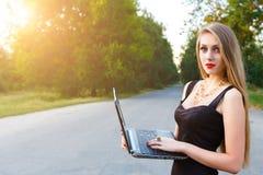 Empresaria hermosa joven que sostiene un ordenador port?til, trabajando en un parque fotos de archivo