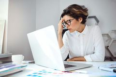 Empresaria hermosa joven que trabaja con el ordenador portátil en el lugar de trabajo en oficina Foto de archivo