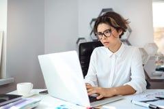 Empresaria hermosa joven que trabaja con el ordenador portátil en el lugar de trabajo en oficina Imágenes de archivo libres de regalías