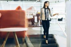 Empresaria hermosa que camina abajo de las escaleras Foto de archivo libre de regalías