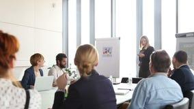 Empresaria hermosa que da la presentación a los colegas que usan el flipchart metrajes