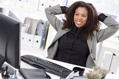 Empresaria hermosa que estira en la sonrisa del escritorio Imagen de archivo