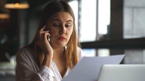 Empresaria hermosa que habla en el teléfono y que discute documentos almacen de video