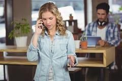 Empresaria hermosa que habla sobre el teléfono en oficina Fotos de archivo libres de regalías