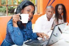 Empresaria hermosa que trabaja en su ordenador portátil en un café Imágenes de archivo libres de regalías