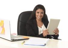 Empresaria hispánica que se sienta en la sonrisa del escritorio del ordenador de oficina feliz usando la tableta digital Foto de archivo libre de regalías
