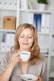 Empresaria Holding Coffee Cup en oficina Imagenes de archivo