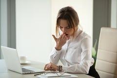 Empresaria impaciente aburrida que bosteza comprobando el tiempo cansado de ove fotos de archivo libres de regalías