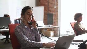 Empresaria india joven que habla en cliente asesor del teléfono en oficina almacen de video