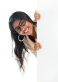 Empresaria india que mira a escondidas de detrás la cartelera en blanco de la muestra Foto de archivo libre de regalías