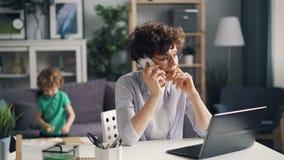 Empresaria infeliz que habla en el teléfono móvil en casa cuando poco hijo está dibujando almacen de video