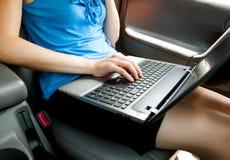 Empresaria irreconocible que se sienta en coche con el ordenador portátil en sus rodillas Fotos de archivo
