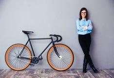 Empresaria joven alegre que coloca la bicicleta cercana Imagen de archivo libre de regalías