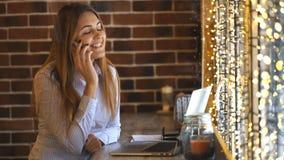 Empresaria joven alegre que habla en el teléfono en un café almacen de video
