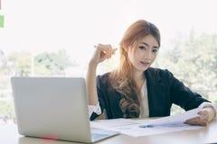 Empresaria joven asiática atractiva que trabaja en el ordenador portátil mientras que sea imagen de archivo libre de regalías