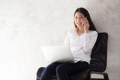 Empresaria joven asiática hermosa emocionada y alegre de éxito con el ordenador portátil Imagen de archivo