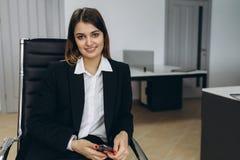 Empresaria joven atractiva elegante con una sonrisa preciosa que se sienta delante de una tabla en la oficina que hace muecas en  foto de archivo