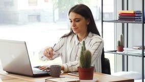 Empresaria joven atractiva que disfruta del trabajo en su oficina almacen de metraje de vídeo