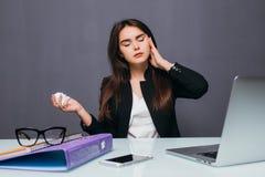 Empresaria joven Blowing Her Nose en Front Of Computer At Desk con dolor de cabeza imagenes de archivo