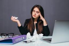 Empresaria joven Blowing Her Nose en Front Of Computer At Desk con dolor de cabeza fotografía de archivo