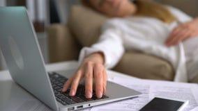 Empresaria joven cansada que duerme en el sofá en la oficina con el ordenador portátil Primer de su mano en el teclado