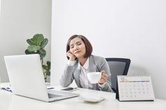 Empresaria joven cansada que tarda un momento para relajarse en su escritorio con sus ojos cerrados y la cabeza que descansa sobr foto de archivo