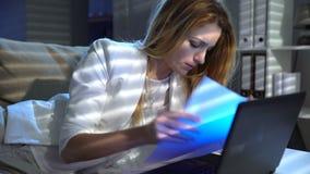 Empresaria joven cansada que trabaja febrilmente en la oficina con el ordenador portátil y los papeles en la noche almacen de video