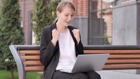 Empresaria joven Celebrating en el ordenador portátil que se sienta fuera de oficina almacen de metraje de vídeo
