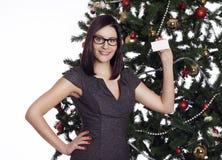 Empresaria joven cerca del árbol del Año Nuevo que sostiene la tarjeta de visita Imágenes de archivo libres de regalías