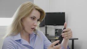 Empresaria joven chocada que recibe noticias de última hora asombrosamente en su smartphone en el trabajo - metrajes