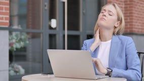Empresaria joven con dolor de cuello usando el ordenador portátil al aire libre almacen de metraje de vídeo